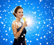 Smiling woman holding glass of sparkling wine. Party, drinks, winter holidays, christmas and celebration concept - smiling woman in evening dress with glass of Royalty Free Stock Image