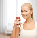 Smiling woman holding glass of tomato juice Stock Image