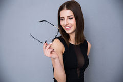 Smiling woman holding glasses over gray background Royalty Free Stock Photo