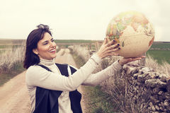 Smiling woman holding a globe. Royalty Free Stock Image