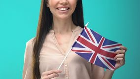 Smiling woman holding Great Britain flag on blue background, education abroad. Stock footage stock video