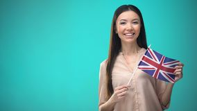 Smiling woman holding Great Britain flag, ready to learn foreign language. Stock footage stock video footage
