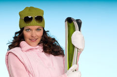 Smiling woman holding green skis Royalty Free Stock Photo