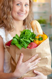 Smiling woman holding a grocery bag Stock Photos