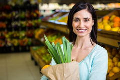 Smiling woman holding grocery bag Stock Photos