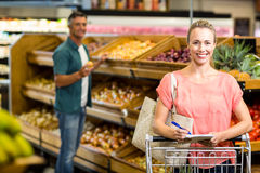 Smiling woman holding the grocery list Stock Images