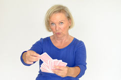 Smiling woman holding a hand of playing cards Stock Image