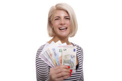 Smiling woman holding a handful of Euro notes. Attractive smiling blond woman holding up a handful of fanned Euro notes in different denominations, tilted angle stock image