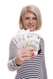 Smiling woman holding a handful of Euro notes. Attractive smiling blond woman holding up a handful of fanned Euro notes in different denominations, tilted angle stock images