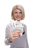 Smiling woman holding a handful of Euro notes. Attractive smiling blond woman holding up a handful of fanned Euro notes in different denominations, tilted angle royalty free stock photo