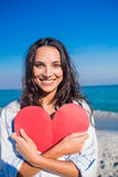 Smiling woman holding heart card at the beach Stock Images