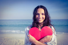 Smiling woman holding heart card at the beach Stock Photos
