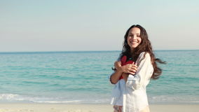 Smiling woman holding heart card at the beach stock video