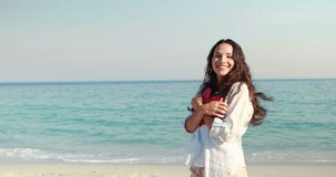 Smiling woman holding heart card at the beach. On a sunny day stock footage