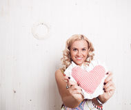 Smiling woman holding heart pillow Stock Photo