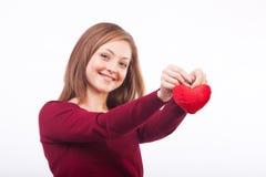 Smiling woman holding heart shape Stock Image
