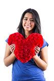 Smiling woman holding a heart shaped pillow Royalty Free Stock Image