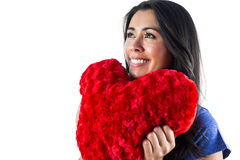 Smiling woman holding a heart shaped pillow Stock Images