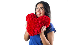 Smiling woman holding a heart shaped pillow Royalty Free Stock Photos