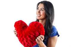 Smiling woman holding a heart shaped pillow Royalty Free Stock Images