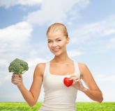Smiling woman holding heart symbol and broccoli Royalty Free Stock Images