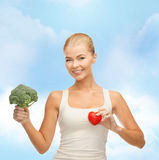Smiling woman holding heart symbol and broccoli Stock Photo