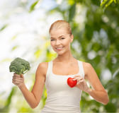Smiling woman holding heart symbol and broccoli Royalty Free Stock Photography