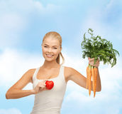 Smiling woman holding heart symbol and carrots Royalty Free Stock Photography