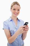 Smiling woman holding her cellphone Royalty Free Stock Images