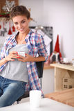 Smiling woman holding her cellphone in the kitchen Stock Photos