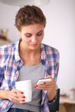 Smiling woman holding her cellphone in the kitchen Stock Image
