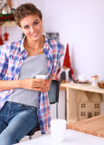 Smiling woman holding her cellphone in the kitchen Royalty Free Stock Images