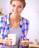 Smiling woman holding her cellphone in the kitchen Royalty Free Stock Photos
