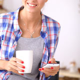 Smiling woman holding her cellphone in the kitchen Royalty Free Stock Photography