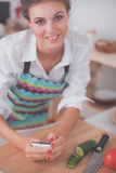 Smiling woman holding her cellphone in the kitchen Royalty Free Stock Photo