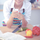 Smiling woman holding her cellphone in the kitchen Stock Images