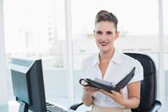 Smiling woman holding her datebook. Looking at camera Royalty Free Stock Image