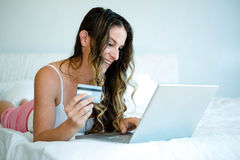 smiling woman holding her laptop and credit card Royalty Free Stock Photos