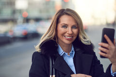 Smiling woman holding her phone on street Royalty Free Stock Images