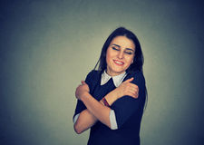 Smiling woman holding hugging herself royalty free stock images
