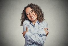 Smiling woman holding hugging herself Royalty Free Stock Photos