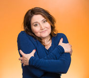 Smiling woman, holding, hugging herself. Closeup portrait happy smiling woman, holding, hugging herself, isolated orange background. Positive human emotion Stock Photography