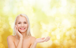 Smiling woman holding imaginary lotion jar Stock Photo