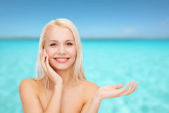 Smiling woman holding imaginary lotion jar Royalty Free Stock Images