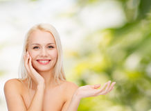 Smiling woman holding imaginary lotion jar Stock Image