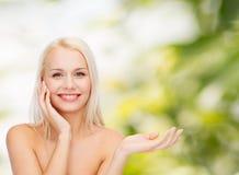 Smiling woman holding imaginary lotion jar Stock Image
