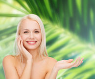 Smiling woman holding imaginary lotion jar Royalty Free Stock Photography