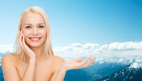 Smiling woman holding imaginary lotion jar Stock Photos
