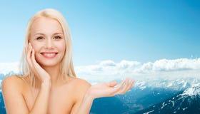 Smiling woman holding imaginary lotion jar Stock Photos