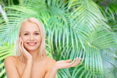 Smiling woman holding imaginary lotion jar Stock Photography